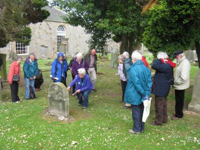 Liz Beevers shows the group an interesting headstone in Currie kirkyard